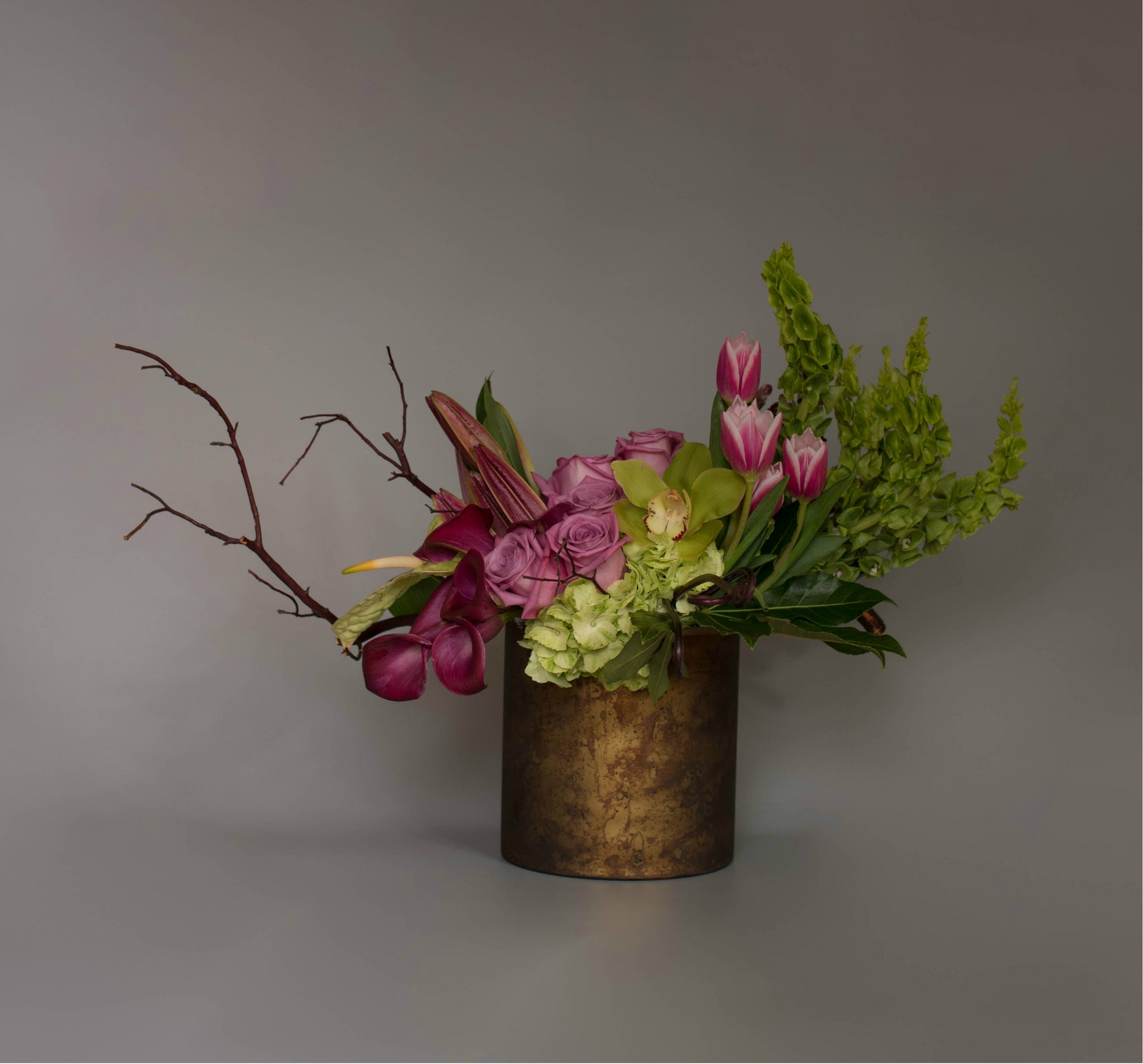 Reaching Manzanita, with grouped florals in copper antiqued container