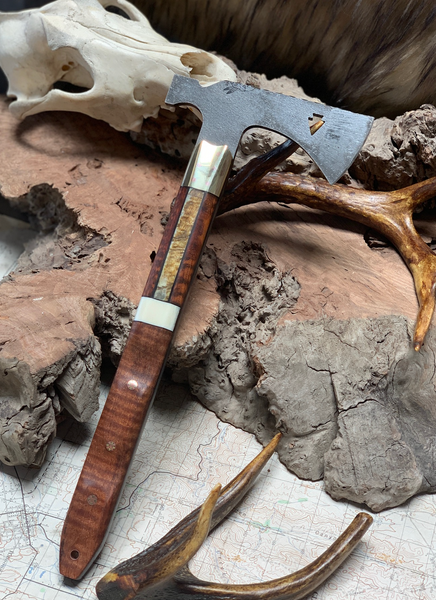 Arrowhead hawk/hatchet, brass bolster split, rams horn between snakewood center split, bastogne walnut with giraffe bone spacer, mosiac pins, solid copper pins, black G10 liners, hollow copper lanyrad pin,