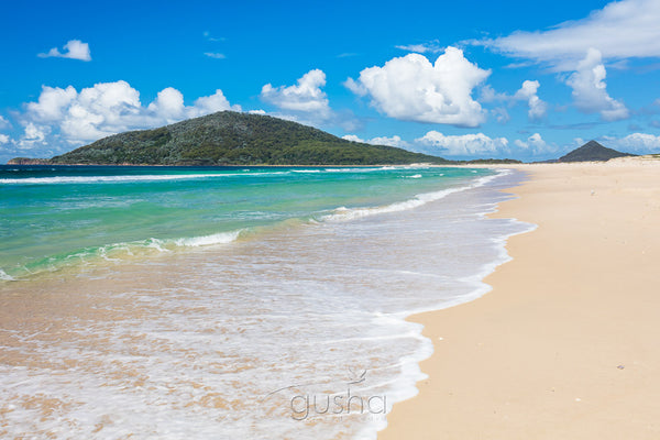 Photographed on the sands of Bennetts Beach, cumulus clouds float slowly behind Yacaaba Headland.
