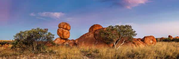 Soft colours at sunset paint the landscape at Karlu Karlu Conservation Reserve, Australia.