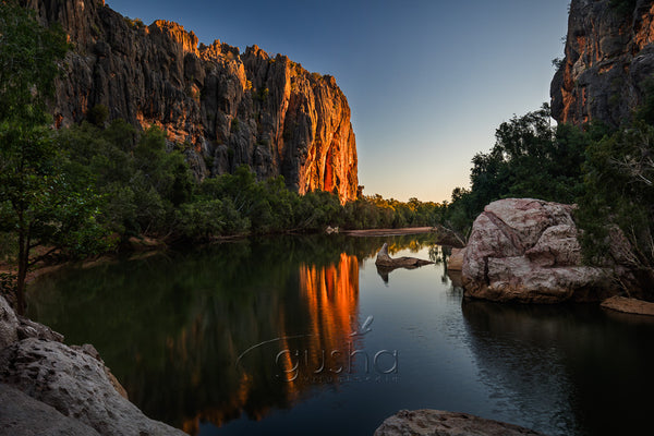 This breath-taking gorge, rises vertically from otherwise flat, outback landscape. The gorge features many lazy, freshwater crocodiles, two can be seen resting on a rock near the centre of this photo.