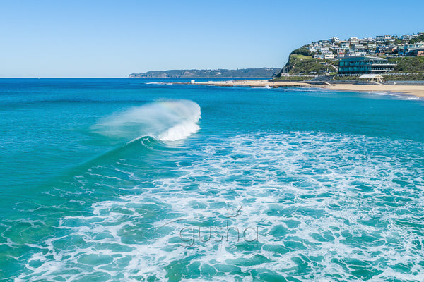 A photo of a wave breaking at Merewether Beach, Australia