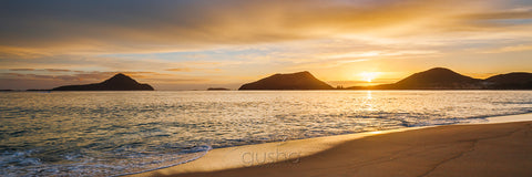 A warm sunrise silhouettes the heads of Port Stephens captured from the shoreline of Shoal Bay.