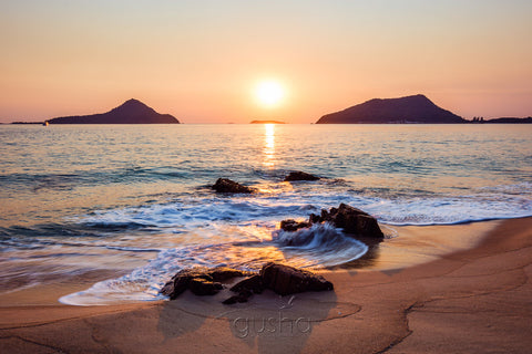 Captured from the sands of Shoal Bay, the sun rises between the heads of Port Stephens, Yacaaba Headland to the left and Tomaree Headland to the right.