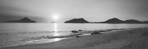 Sunrise silhouettes the heads of Port Stephens from the sands of Shoal Bay.