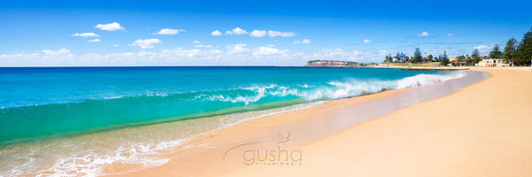 A perfect shorebreak rolls onto the sands of Collaroy Beach.