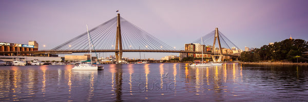 A photo captured at dusk of Anzac Bridge over Sydney Harbour.