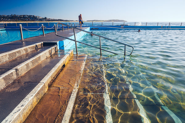 A photo of steps into sparkling water at the edge of Dee Why Pool in Sydney, Australia.