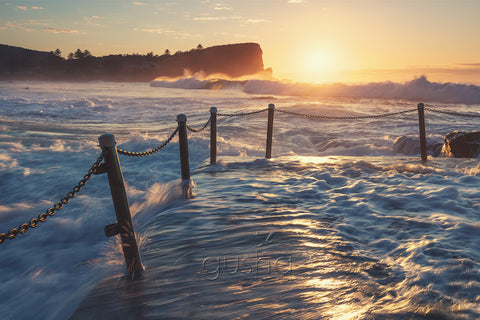 A photo of ocean water rushing over Avalon Beach pool at sunrise in Sydney, Australia.