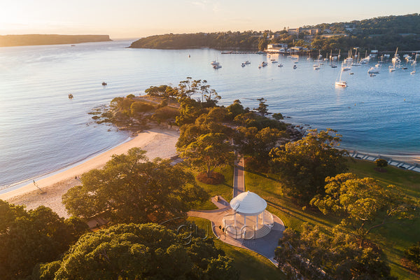 In this photo the early morning sun is rising over the rotunda and Balmoral Beach in Sydney, Australia.