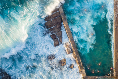 An overhead photo of large surf crashing over the pool and swimmers at Avalon Pool in Sydney, Australia.