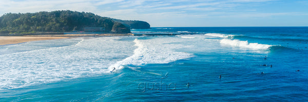 Photo of surfers on waves at North Narrabeen Beach