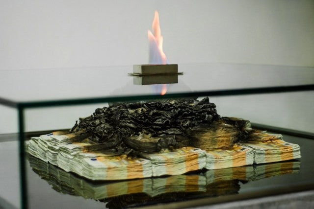 This Coffee Table Features Burning Stacks of Cash