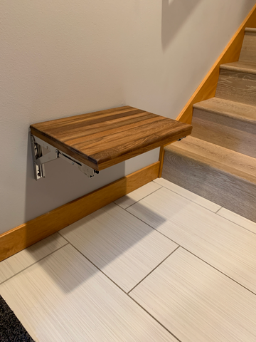Folding wall mount bench mounted at the bottom of stairs by a door to use as a seat to put on or take off shoes.