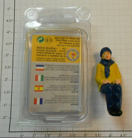 Elita Modelle 10060 Man Siting With Yellow Coat And Blue Scarf