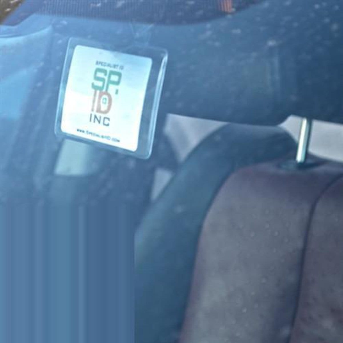 Hang tag holder shown through car windshield handing on rear view mirror
