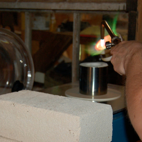 holding torch on the metal about to pour in the hot flask on the casting vacuum table