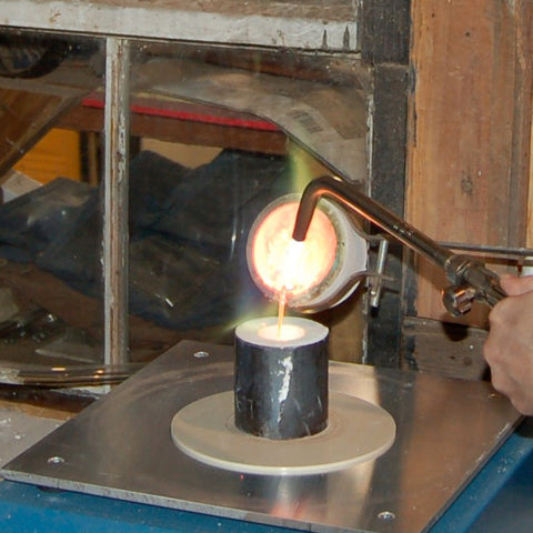 pouring molten metal in to a flask on the casting vacuum table for lost wax casting