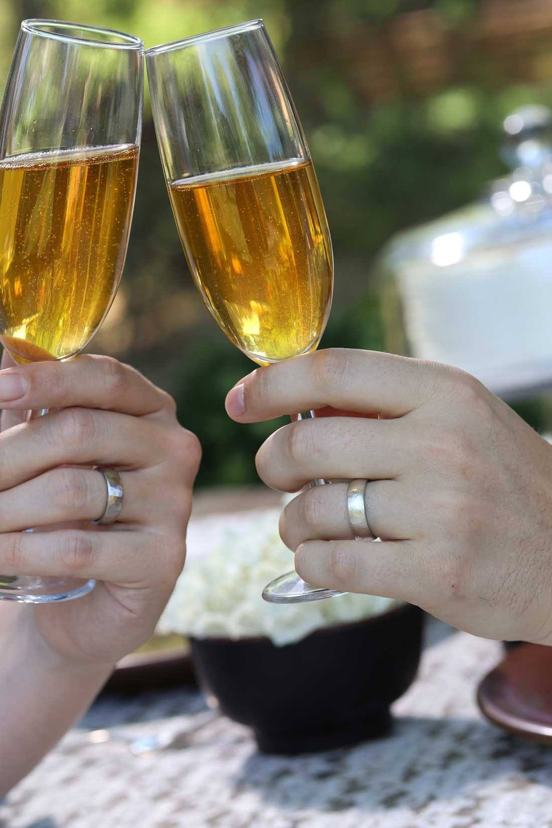 Worn and Hammered Texture Wedding Bands on hand toasting with cider - rings handmade by Beth Cyr
