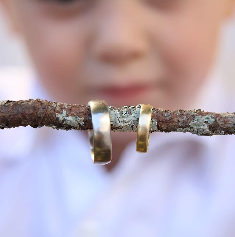 Simplicity Rings handcrafted by beth cyr in gold alloys hanging on stick held by little boy