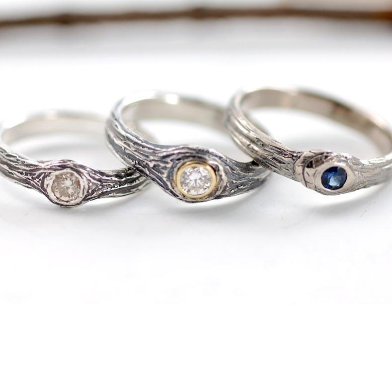Tree Bark Rings in palladium sterling silver with diamonds, yellow gold setting and 14k palladium white gold with blue sapphire by Beth Cyr