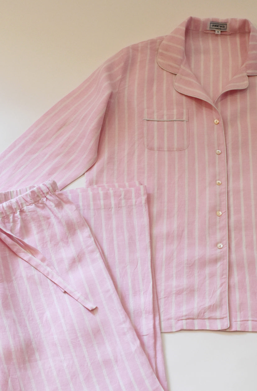 Pink and white stripe linen pajama set with seam free trousers, mother of pearl buttons and cord piping.