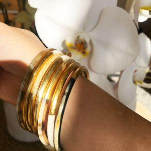 wearing a set of golden buffalo horn bangle next to white orchid flower
