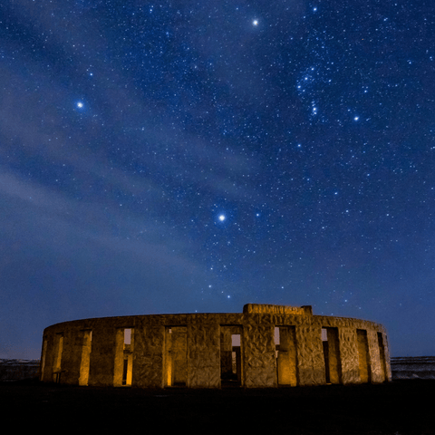 starry night sky with ancient building softly lit