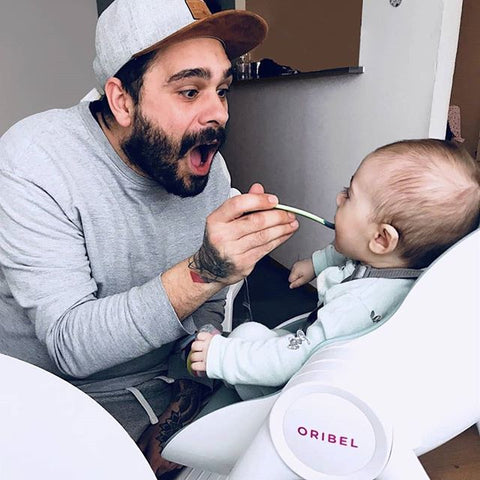 daddy feeding his baby during meal time in the Cocoon high chair