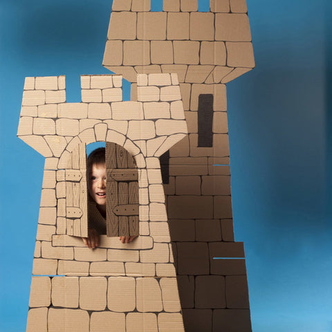 child looking out the window of a handmade cardboard castle