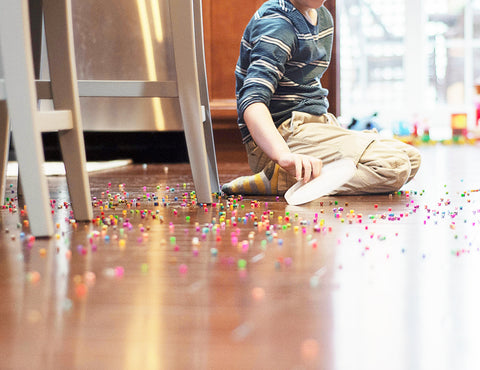 kid sitting down on a floor with spilled beads