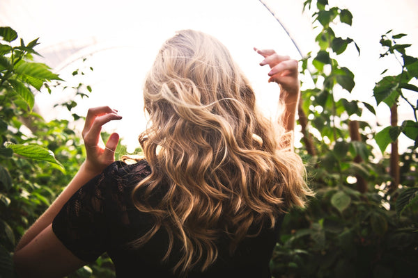 Best all-natural shampoo: Woman with long blonde hair stands in the sunlight