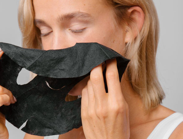 Natural Toner: Woman applying black charcoal sheet mask
