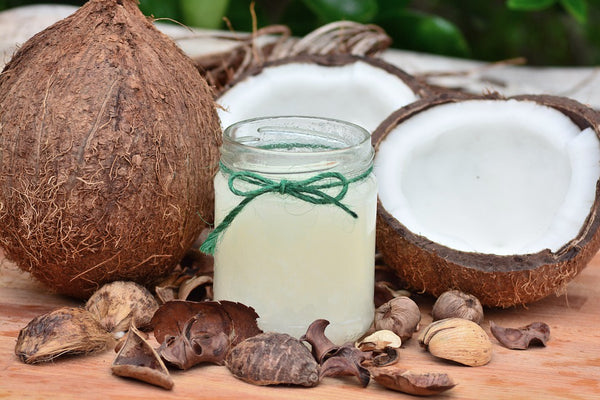 Natural skin moisturizer: a jar of coconut oil surrounded by tropical coconuts