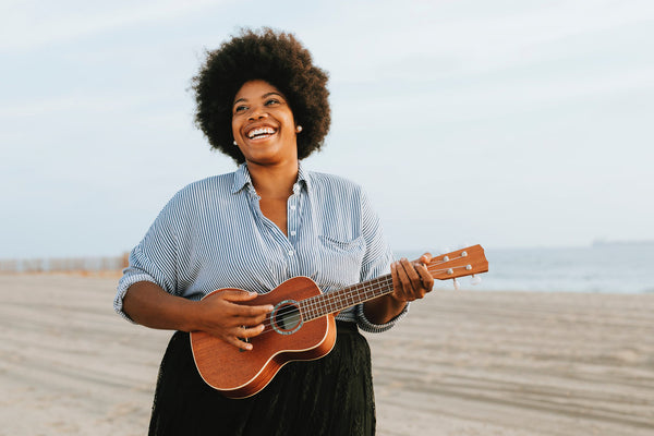 Moisturizer for sensitive skin: A radiant, happy woman plays the ukulele on the beach