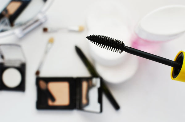 Chemical-free makeup: a mascara wand in the foreground with makeup palettes in the background