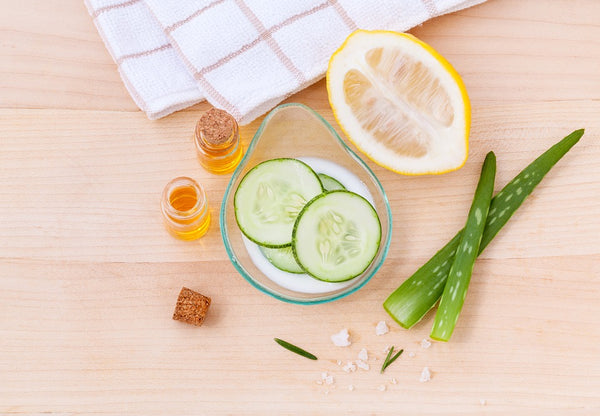 Natural Toner: Cucumbers, lemon, aloe, and jar of liquid on a table