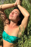 Woman meditating in the sun wearing Aqua tie dye Bandeau Top made of organic cotton.
