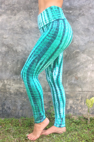 Long length yoga pants turquoise/teal tie dye. Fold over top for adjustable fit can be worn with higher waist or lower on the hips. 90% cotton 10% spandex. side view