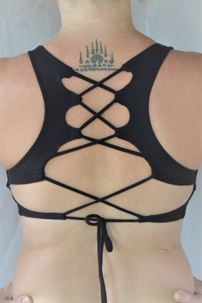 Solid black yoga crop top bra that accentuates the natural beauty of a woman's back with light support and lace up corset back, perfect for festival season.