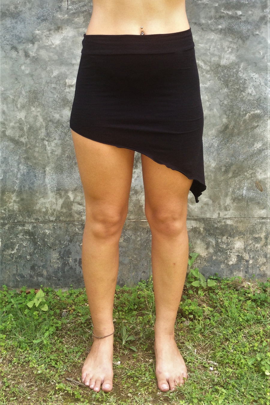 Front view of Festival Skirt by Lotus Tribe Clothing is a stretchy asymmetrical, easy to wear comfortable mini skirt. Looks great over bare legs or can be layered with leggings in cool er weather. Fold the top over or wear high waisted, custom form fits to your body shape. Soft and stretchy 90% cotton knit with 10% spandex.