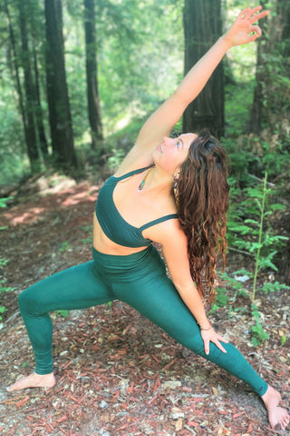 Woman wearing Forest green Yoga Pants and matching Sports Bra in the woods in a yoga pose.