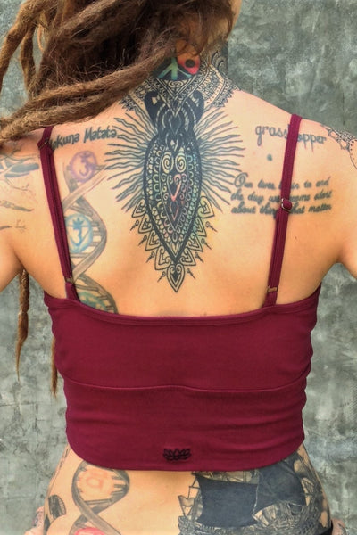 Back of organic cotton crop tank with adjustable spaghetti straps and scrunched center puckering between the breasts in solid Garnet color with small black Lotus Flower embroidery.