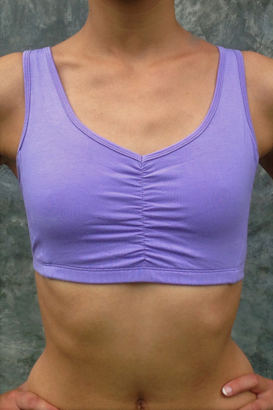Front view of Lavender Sports Bra that has wide straps and ruching between breasts. Has sunburst design straps on back. Comes in sizes XS-XL but especially great for large chested active women while still being soft, cute, comfortable and functional.