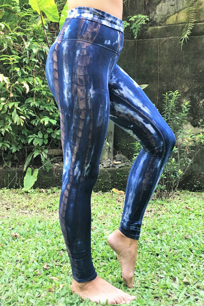 Side view of Organic Yoga Pants in Indigo Earth tie dye, dark blue with brown streaks and white highlights. Made of 90% Organic Cotton with 10% Spandex, extra long length and high waist that can be folded over for custom fit.