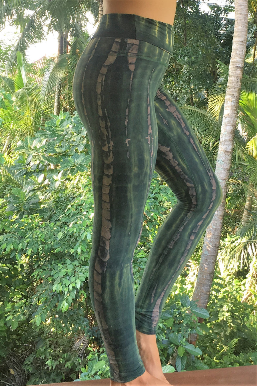 Side view of Organic Yoga Pants in RainForest tie dye with fold waist top can be worn high or folded down onto hips for custom fit. Green hues with beige streaks.