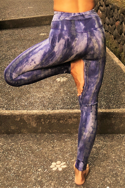 Woman in tree pose wearing fold over waist yoga pants in cool purple hues with grey and white highlights.