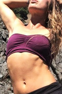 Tan fit woman wearing Plum Bandeau by Lotus Tribe Clothing. Shows solid color, strapless, with puckering at center