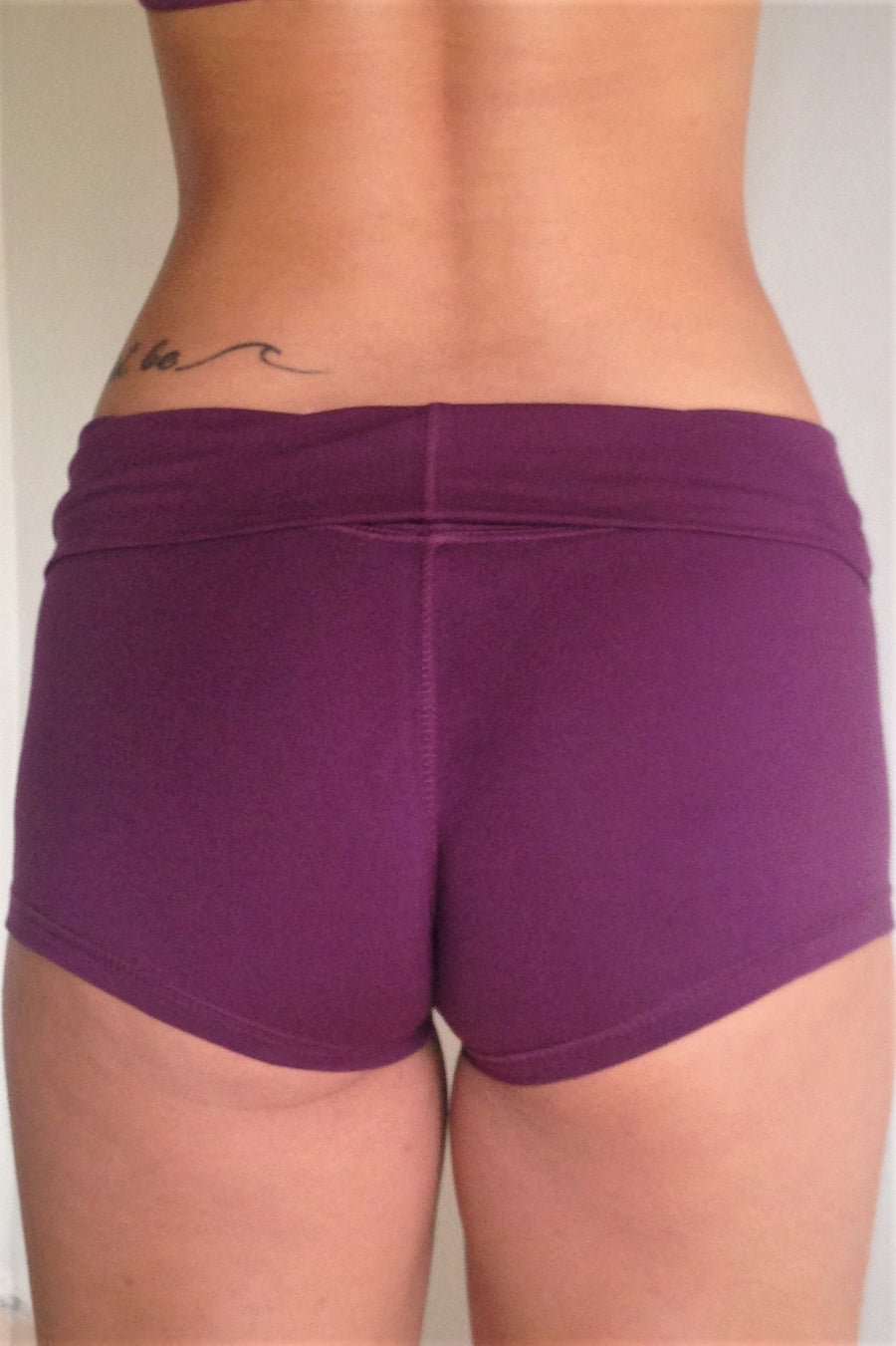 Back view of solid Plum purple yoga shorts with fold over waist, can be worn higher waisted, or low on the hips. Small black Lotus Flower embroidery. 90% cotton 10% spandex.