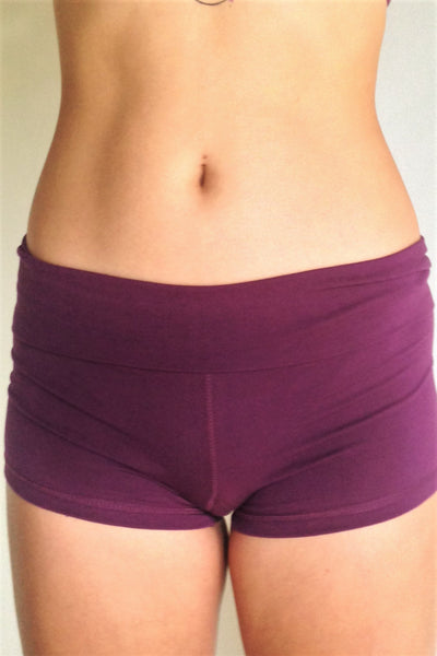 Front view of solid Plum purple yoga shorts with fold over waist, can be worn higher waisted, or low on the hips. Small black Lotus Flower embroidery. 90% cotton 10% spandex.
